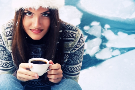 Christmas teen girl attractive drinking coffee over winter nature background photo