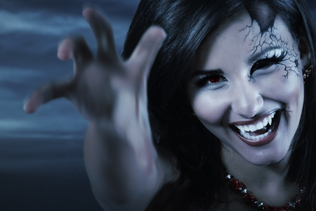 woman beautiful halloween evil vampire over night background photo