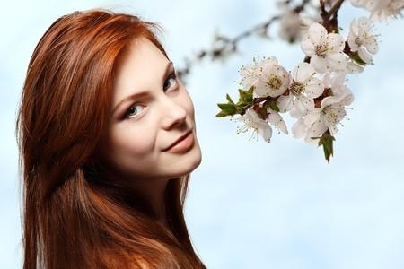 pelo rojo: hermosa chica adolescente de pelo rojo alegre disfrutando más de fondo de flores de primavera