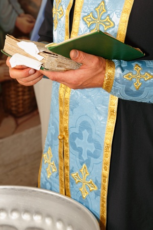 Bible in hands of holy father in church photo