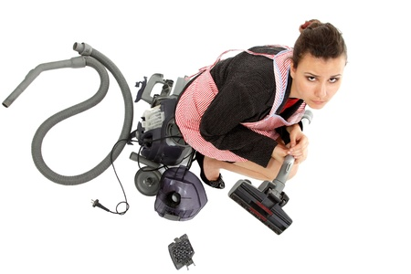 businesswoman and housewife tired in apron with broken vacuum cleaner isolated on white background photo