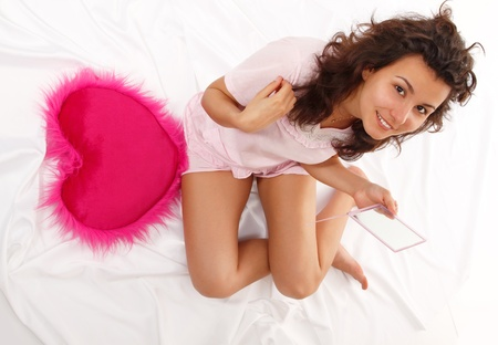 teen girl cheerful beautiful with mirror in bed photo