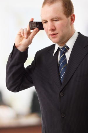smiing: young businessman speaking mobile phone in office