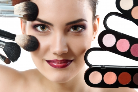 beauty portrait of young beautiful woman with makeup brushes and palette of eye shadows isolated on white background photo
