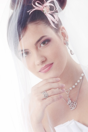 hairdress: beauty young bride with beautiful makeup na hairdress in veil over white background
