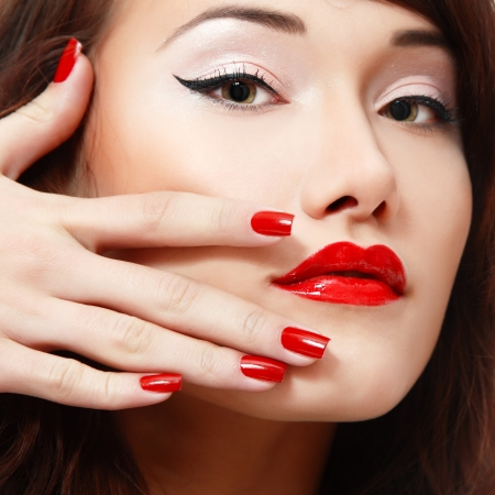 beautiful young female face with vivid red lipstick and nail polish closeup photo