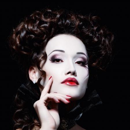 woman beautiful halloween vampire baroque aristocrat over black background photo