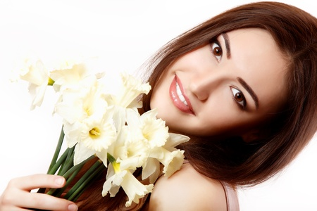 teen girl brown hair: beautiful teen girl smiling and with flower narcissus and looking at camera. isolated on white