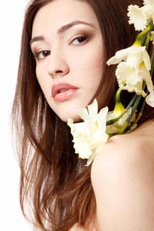 beautiful teen girl smiling and with flower narcissus and looking at camera. isolated on white photo