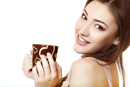 portrait of young beautiful woman hoolding cup of tea or coffee with hearts and happy smiling. isolated on white background. photo