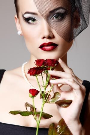 mujer con rosas: Hermosa mujer con flores rosas de color rojo oscuro con un velo de belleza retro retrato de glamour. Cara primer plano