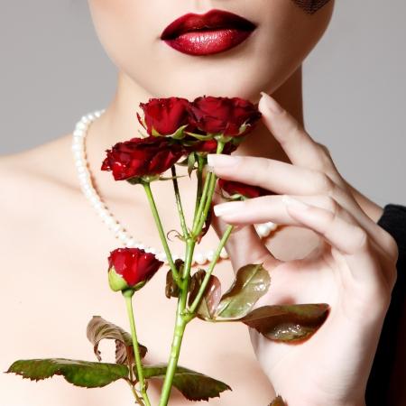 labios sensuales: Mujer hermosa con la flor oscura rosas rojas en velo glamour retro retrato de la belleza. Primer de la cara