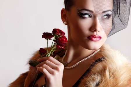 Beautiful woman with dark red roses flower in veil and fur coat retro glamour beauty portrait. Face closeup photo