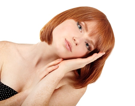 portrait of young beautiful redheaded woman hoolding hand near her face. isolated on white background. photo