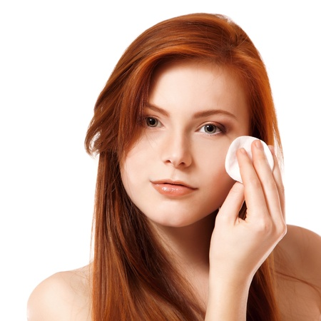 Portrait of beautiful young redheaded woman delete cosmetics with makeup sponge. Isolated on white background photo
