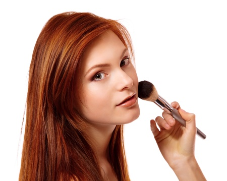 Portrait of beautiful young redheaded woman with esthetician making makeup. Isolated on white background photo