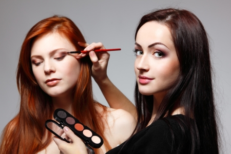 Portrait of beautiful young redheaded woman with esthetician making makeup eye shadow photo