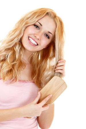 combing hair: Young cheerful blond woman combing hair. Isolated on white background