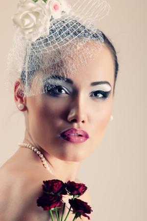 Hermosa mujer con flores rosas de color rojo oscuro con un velo de belleza retro retrato de glamour. Cara primer plano