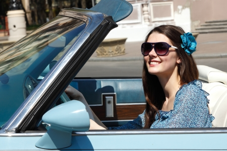 Young beautiful woman drive retro car in summer city photo