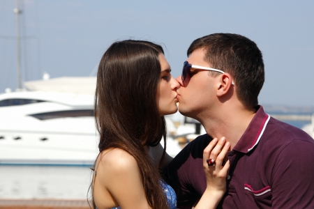 young beautiful caucasian couple hugs and kiss - first love in seaport photo