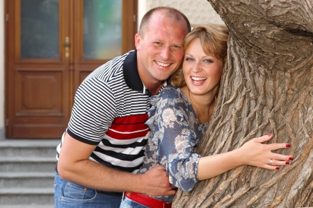 hugs and kisses: Happy attractive mid adult couple have fun outdoor. Wife and husband near tree in city park Stock Photo