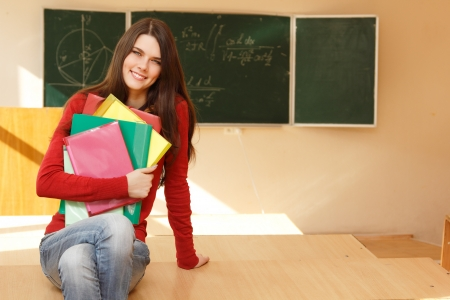 achiever: beautiful teen girl high achiever in classroom near desk happy smiling