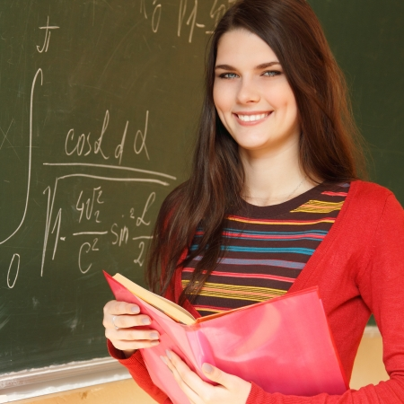 achiever: beautiful teen girl high achiever in classroom near desk with formulas of higher mathematics