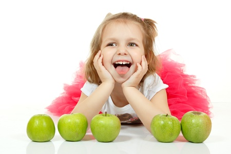 girl lying studio: Cute little girl playng with apples and show tongue. Isolated on white background Stock Photo