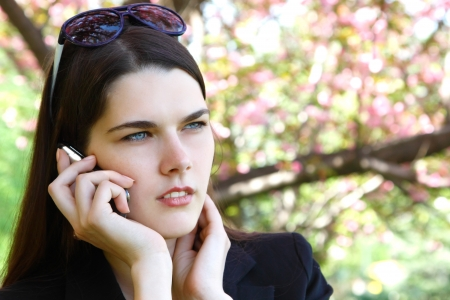 untidiness: beautiful troubled girl calling phone over blooming spring garden