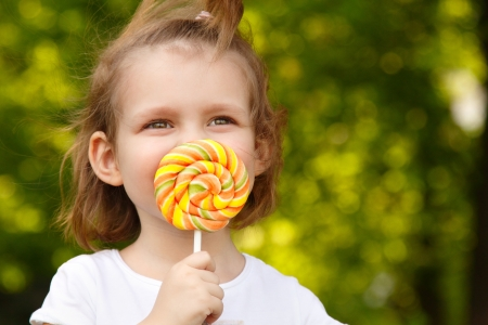 happy little girl with sweet candy nature summer outdoor photo