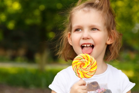 happy little girl licks sweet candy nature summer outdoor photo