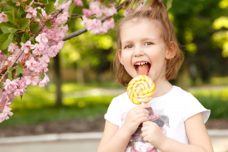happy little girl licks sweet candy nature summer outdoor Stock Photo - 15153803
