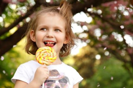 happy little girl licks sweet candy nature spring outdoor photo