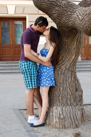 young couple hug and kiss over summer city outdoor photo