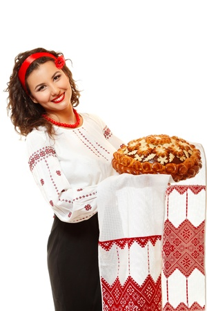 bead embroidery: Beautiful ukrainian young hospitable woman in native costume by tradition holding embroidered towel and round loaf, on white background