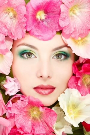 beauty portrait of beautiful female face with pink, red and white mallow flowers frame  Stock Photo