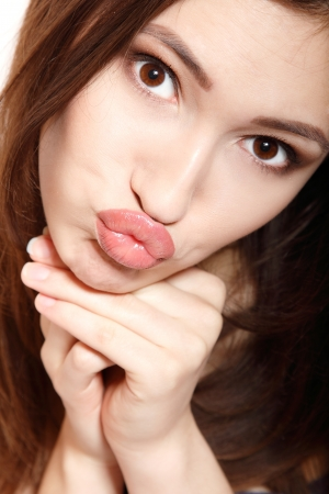teen girl brown hair: teen girl make faces with kiss looking at camera isolated on white background