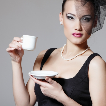 Beautiful woman in veil retro glamour beauty portrait with cup of tea or coffee photo