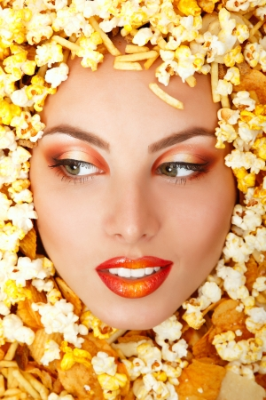 eating popcorn: woman beauty face with unhealth eating fast food popcorn potato chips rusk frame Stock Photo