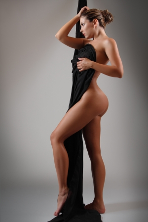 naked woman back: perfect body of sexy nude young woman with black fabric, studio shot
