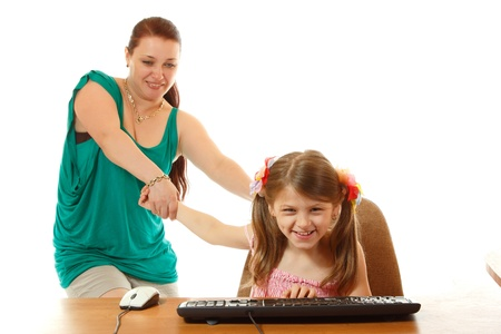 girl with internet dependence playing with keyboard being dragged by mother from her computer, isolated on white