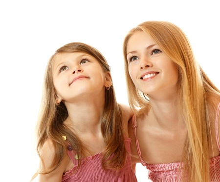 sudio: portrait of two sisters happy smiling (child and teen) looking up to corner, isolated on white background Stock Photo