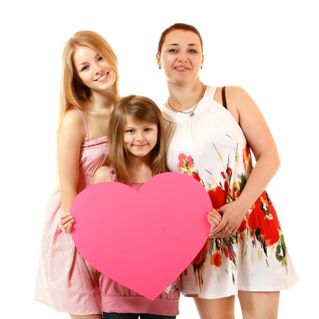 blonde mom: happy mother with two daughters holding big heart, isolated on white background