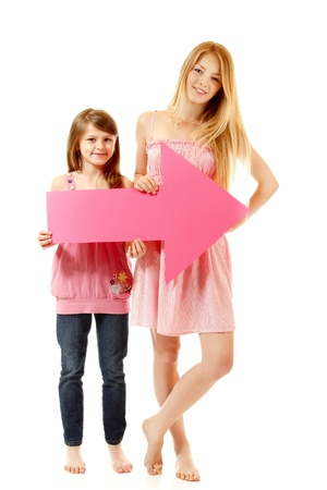 sudio: two sisters happy smiling hplding pink arrow, isolated on white background