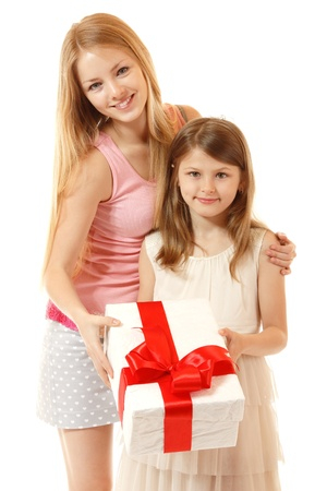 happy little girl holding christmas present with her sisiter, isolated on white background photo