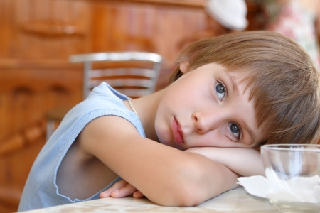 occhi tristi: Pensieroso bambino seduto a tavola e in attesa di mangiare