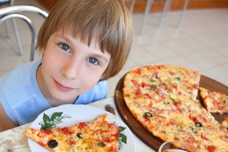 plato del buen comer: Niño feliz que se sienta a la mesa y comer pizza