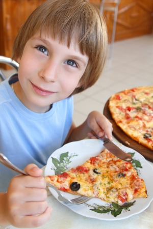 Happy little boy sitting at table and eating pizza photo