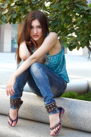 young teen girl: Outdoors street portrait of beautiful young brunette girl near tree